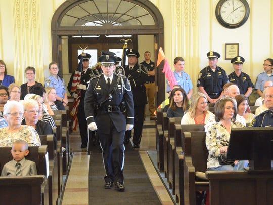 Lt. Steve Bush leads the police department honor guard to begin the program.