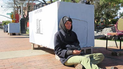 In this Feb. 25, 2015 photo, Sonny Clenny, 29, sits near a dream pod in downtown Tucson, Ariz., at a park where protesters have made a permanent home. The protesters at Veinte de Agosto Park say the growing encampment on a small, one-acre green space is a way to combat city regulations they believe unfairly target the homeless.