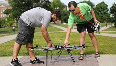"""University of Cincinnati Aerospace Engineering students Wei Wei (cq), right, and Bryan Brown (cq) turn on their mini-drone, called an """"Octocopter"""" on Thursday, June 19, 2014. It's a prototype they're developing for a local company that eventually wants to use it to make remote deliveries off the roofs of delivery trucks."""