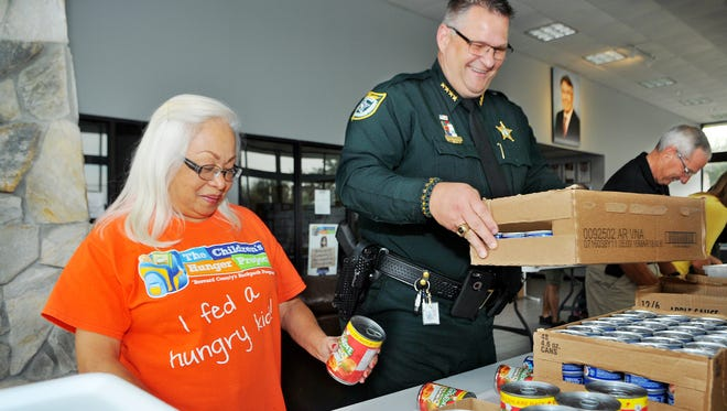 Cora Brown of Melbourne and a volunteer with the Children's Hunger Project, and Brevard County Sheriff Wayne Ivey pack up weekend backpack meals for children in the area during a private packing party at the Children's Hunger Project office in West Melbourne.