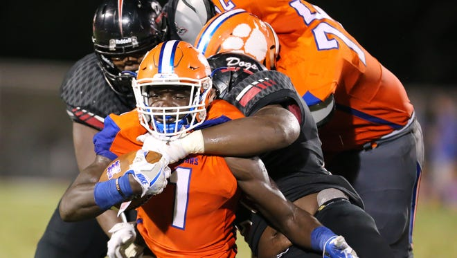 Madison Central's Tyshaun White (1) is wrapped up by two Brandon defenders in the first half.