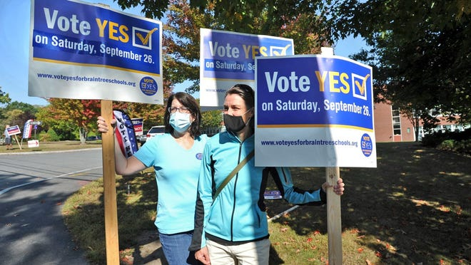 Lisa Fiske Heger, left, and Meredith Boericke hold signs outside the South Middle School in Braintree during a special election urging voters to approve a proposed $63 million debt exclusion that would fund a new South Middle School and othe school upgrades, Saturday, Sept. 26, 2020. Tom Gorman/For The Patriot Ledger
