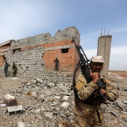 Iraqi security forces rest next to a damaged house in the southern entrance of the city of Tikrit on Sunday during a military operation to retake the northern Iraqi city from Islamic State (IS) group. IS released a new video on Sunday that purports to show the execution of eight Shiite muslims as it fights in Syria and Iraq.