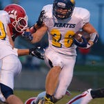 Pewamo-Westphalia's Jared Smith (26) rushes against Laingsburg's Dan Harkness, left, and Cole Blankenship, bottom, as P-W's Reece Platte (60) blocks Friday, Oct. 9, 2015, in Laingsburg, Mich. Pewamo-Westphalia won 50-7.
