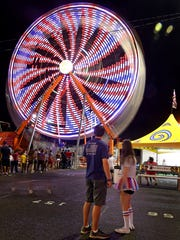 The Ferris wheel creates brilliant colors as it spins on the midway at the Tennessee State Fair on Sept. 17, 2016.