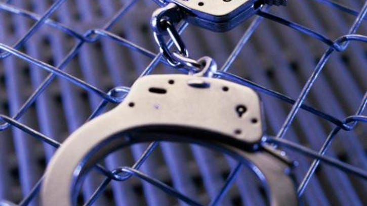 Close-up of a pair of handcuffs on a chain-link fence