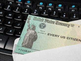 Government-issued check lying on a computer keyboard.