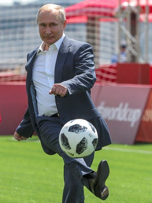 Russian President Vladimir Putin kicks the ball during an opening friendly soccer match between two children teams and FIFA legends at a Football Park in Red Square.