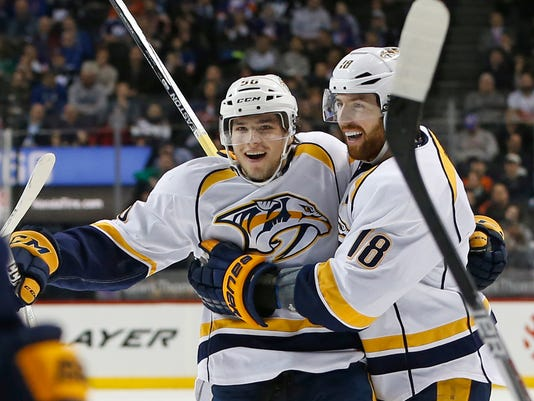 Nashville Predators left wing Kevin Fiala (56), of Switzerland, celebrates with Predators right wing James Neal (18) after scoring on New York Islanders goalie Thomas Greiss in the first period of an NHL hockey game in New York, Monday, March 27, 2017. (AP Photo/Kathy Willens)