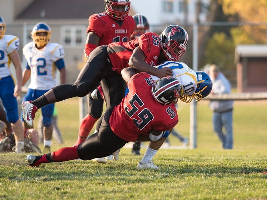 William Penn's Charles Hope and Collins Adu-Gyamfi (59) tackle Drew Morris of Sussex Central during the Colonials' first-round playoff win.