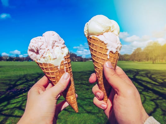 Young couple with Ice Creams in the park.