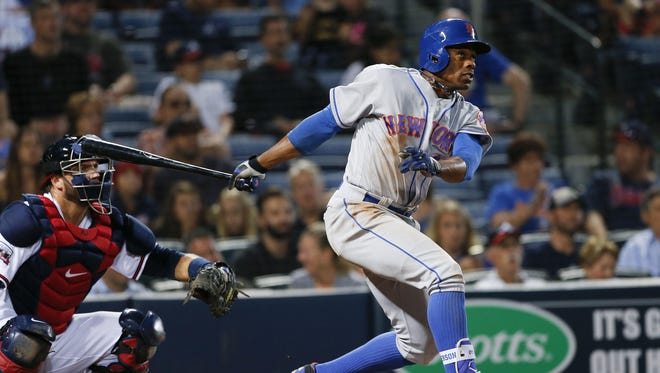 New York Mets' Curtis Granderson (3) follows through with a grand slam as Atlanta Braves catcher A.J. Pierzynski, left, looks on in the second inning of a baseball game Friday, April 22, 2016, in Atlanta . (AP Photo/John Bazemore)