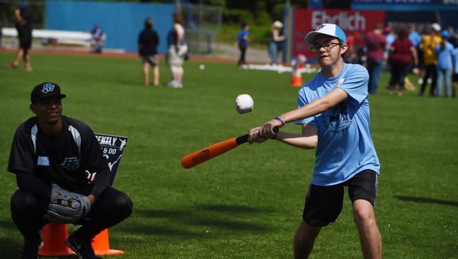 "Caleb M., right, of the Town of Poughkeepsie, swings at the ball while the Renegades' Oscar Rojas, left, acts as a catcher at the hitting station during the ""Disability, Dream & Do"" camp at Dutchess Stadium in Fishkill."