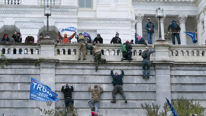 Supporters of President Donald Trump climb the west wall of the the U.S. Capitol on Wednesday, Jan. 6, 2021, in Washington. A bill co-sponsored by Rep. Fred Upton, R-St. Joseph, aims at cracking down on domestic terrorism, with a focus on white supremacy.