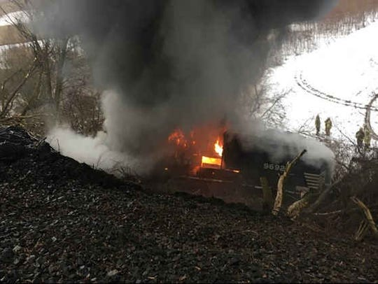 A Norfolk Southern engine burns after a train derailed