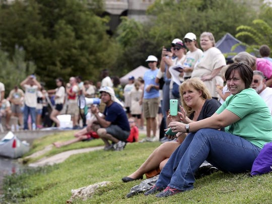 Adam Sauceda/Standard-Times file River Fest visitors line the shore to watch events such as canoe and river raft races in 2015.
