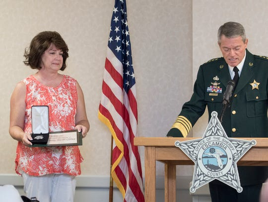 Jill Heddy listens as Sheriff David Morgan posthumously
