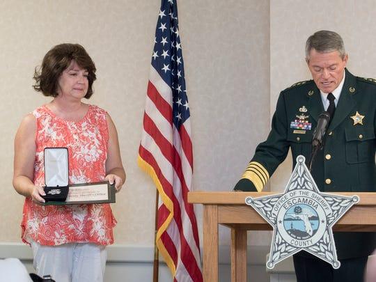 Jill Heddy listens as Sheriff David Morgan posthumously