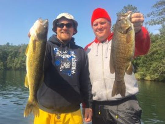 Dustin Hofler, left and Pat Flair how a walleye and smallmouth bass, respectively.