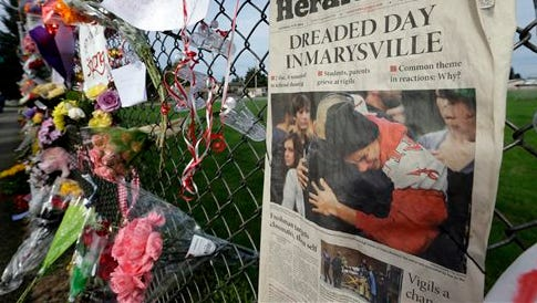"""In this photo, an edition of The Daily Herald from Everett, Wash. with the headline """"Dreaded Day in Marysville"""" is shown as part of a growing memorial on a fence around Marysville Pilchuck High School in Marysville, Wash. On Wednesday, authorities released the 911 calls from students, parents, neighbors, school workers and teacher Megan Silberberger, who tried to intervene when a freshman student, Jaylen Fryberg, opened fire at a group of friends at the school on Oct. 24."""