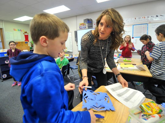 Second grade teacher Peggy Empey works with student