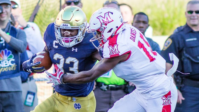 Notre Dame Fighting Irish running back Josh Adams (33) stiff arms Miami (Oh) Redhawks defensive back Deondre Daniels (15) in the first quarter of the game at Notre Dame Stadium.