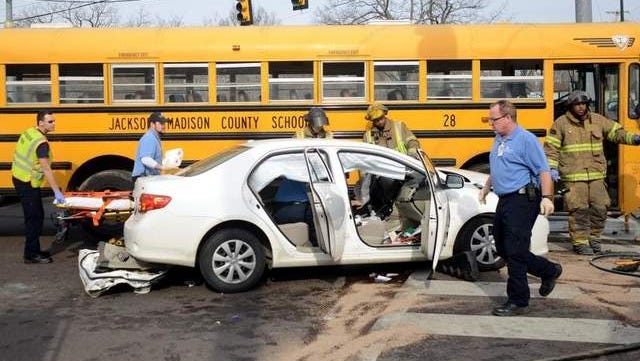 Jackson firefighters and EMS respond to an accident involving a car and a school bus at the intersection of North Royal Street and Lane Avenue on Friday. The man driving the car, Madison Academic band director Michael Congiardo, died after he was transported to the hospital. No students were on the bus, and the bus driver was not injured.