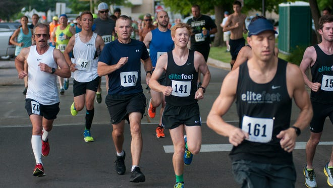 Runners take off at the start Sunday, June 26, during the Blue Water Half Marathon in Port Huron. Brad Mallory (big No. 141) finished first overall with a time of 1:15:57.