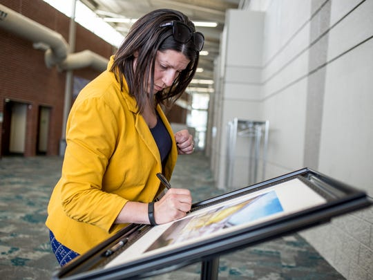 District Court Administrator Andrea Strassburg writes a farewell note on the frame of a piece of artwork that will be gifted to St. Clair County Administrator Bill Kauffman during his retirement party Thursday, May 26, 2016 at the Blue Water Convention Center. Kauffman is retiring after 26 years working for the county.