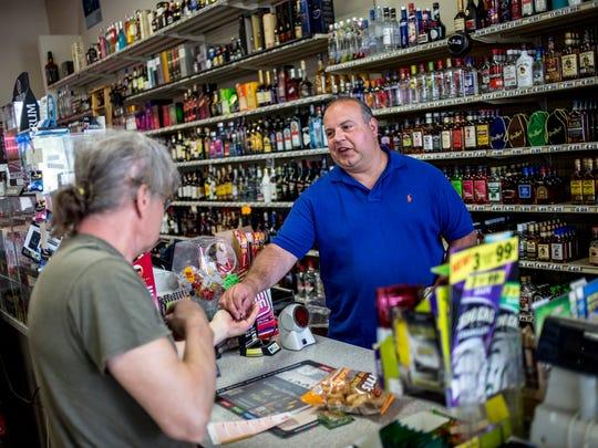 Owner Sal Dado hands customer Ron Kubbe, of Kimball