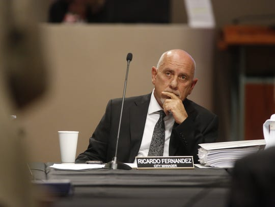 City Manager Rick Fernandez listens to Erwin Jackson's