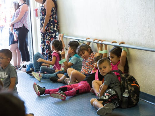 Students in last year's K-3 Plus program wait for transportation after school was dismissed on July 23, 2018. School ended early that day due to unusually high temperatures that day.