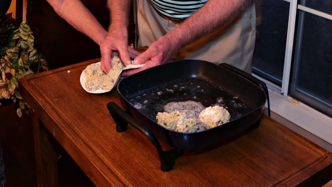 Top Home Chef contestant Jo Birlin oversees her husband Larry while he prepares pan fried risotto cakes table side, as seen in Sun Lakes on April, 8, 2015