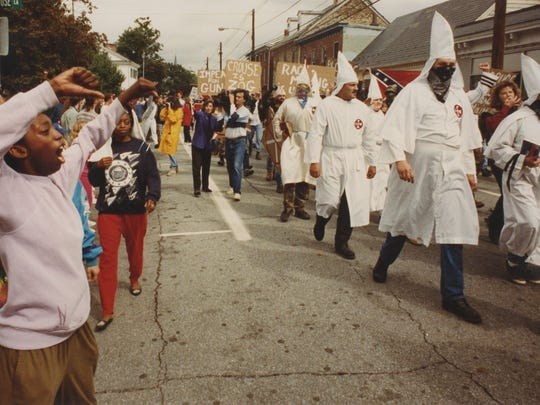 A counterprotester expresses opinion as Ku Klux Klan members march down Main Street in Elkton, Md. on Sept. 26, 1992.