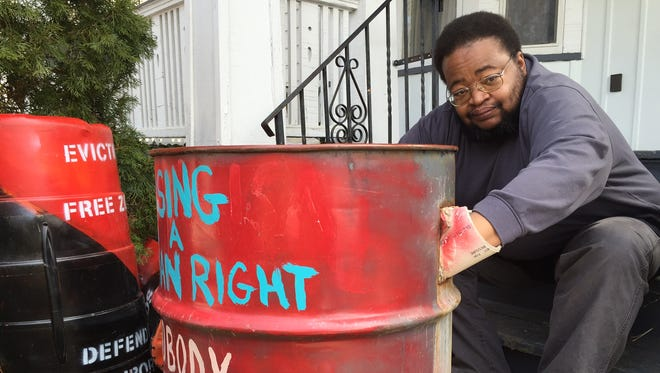 George Douglass sits in front of his home with his concrete drum.