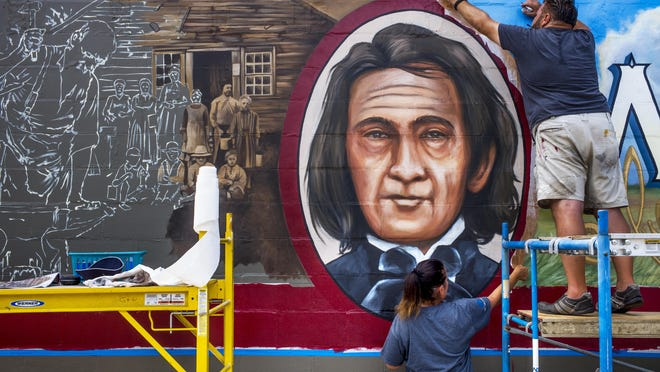 Walldog artists Doug Haffner, right, of Wyoming, and Anat Ronen, of Houston peel away a protective layer used to form a precise framing of a portrait of Washington founder William Holland adjacent to an unfinished portion at left of a large mural on the side of a building in Washington Saturday, July 11, 2020. Production of the mural is one of several events held to kick off a series of events over the next five years leading to the 2025 celebration of the Tazewell County communities bicentennial celebration.