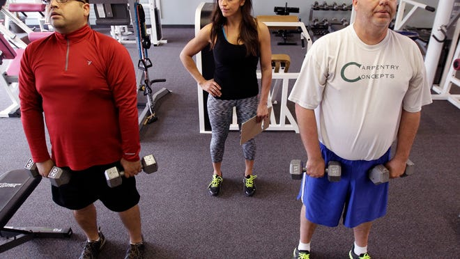 Ricardo Arguello (left) and Mike Sherry workout under the watch of trainer Maria Munoz at Evolve Personal Training in Appleton. It was the first workout of a 10-month fitness program that Arguello and Sherry will share via social media and on the pages of The Post-Crescent.