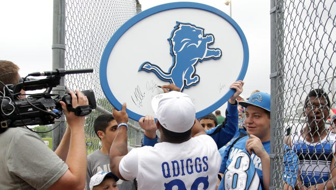 Detroit Lions cornerback Quandre Diggs signs autographs during the team's annual charity softball game on June 5, 2015, in Dearborn.