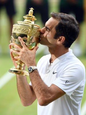 Roger Federer of Switzerland kisses the championship trophy following his victory over Marin Cilic of Croatia in Wimbledon.