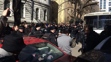 People block the way for a police bus in the area where Alexei Navalny was being held in downtown Moscow on Sunday.