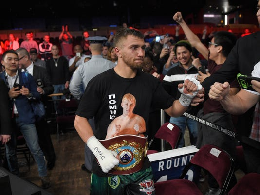 FILE - In this April 9, 2017, file photo, Vasyl Lomachenko interacts with fans after a boxing match against Jason Sosa, not shown, in Oxon Hill, Md. Lomachenko is training in California farming country for his WBO junior lightweight title bout against Miguel Marriaga on Saturday, Aug. 5, 2017. The two-time Olympic gold medalist from Ukraine enjoys the tranquility of his quiet American surroundings. (AP Photo/Nick Wass, File)