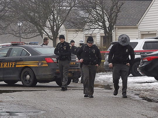 Police investigate the scene of a shooting in Westerville, Ohio, on Saturday, Feb. 10, 2018.  Westerville police have confirmed that two officers have been fatally shot at a home in the Columbus suburb.  A police statement says the officers responded to a 911 hang-up call around 11:30 a.m. and were shot after they arrived at a residence.  A suspect is reportedly in custody.