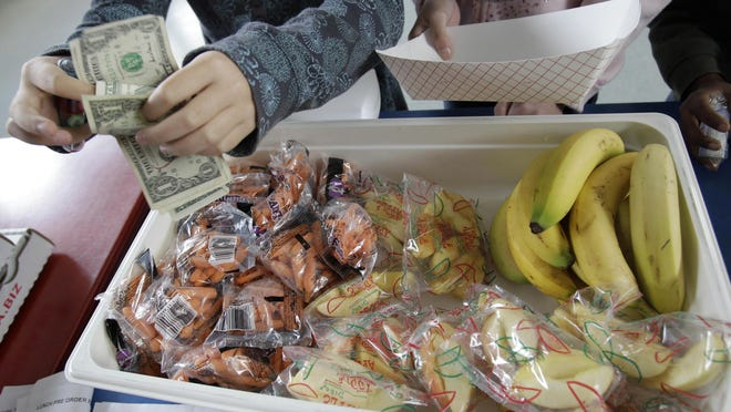 """FILE – In this Dec. 2, 2010, file photo, a child pays for a lunch consisting of fruits and vegetables during a school lunch program at Fairmeadow Elementary School in Palo Alto, Calif. California and Pennsylvania both passed laws in 2017 to outlaw """"lunch shaming"""" of children for unpaid meals, with the Pennsylvania measure that became law in November requiring communication about money owed on meal accounts to be done between school officials and parents, and not involve the student. (AP Photo/Paul Sakuma, File)"""