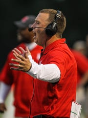 Newport head coach Matt Schmitz yells to his Wildcats during a football game.