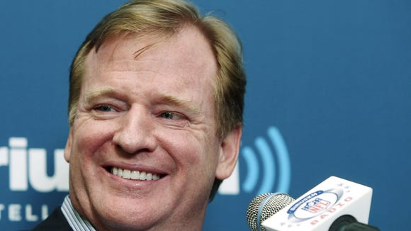 NFL Commissioner Roger Goodell smiles as he talks with former New York Giants defensive end Michael Strahan, not shown, and football fans during a Sirius XM Town Hall event in New York on Oct. 22, 2012.
