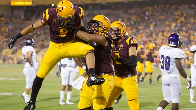 ASU running back D.J. Foster celebrates a touchdown during the third quarter of a game against Weber State at Sun Devil Stadium in Tempe, Ariz. on Aug. 28, 2014.