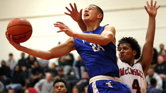 Cedar Crest's Cole Laney (25) goes to the hoop as McCaskey's Gregory Nunez (4) defends during first half action of an LL section 1 showdown at McCaskey High School Friday December 18, 2015.
