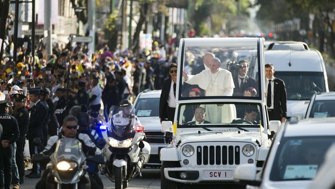 Pope Francis goes by hundreds of thousands of people en route to the basilica in Mexico City, Mexico, Feb. 13, 2016.