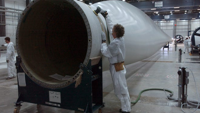 Bruce Nordell, a blade technician at Vestas in Windsor, sands the root of a wind turbine blade in this 2010 file photo.