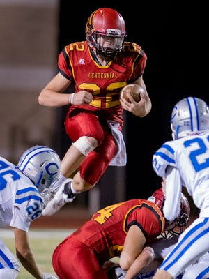 Centennial quarterback Lance Frost hurdles the Cavemen's defensive line for a 3 yard gain Friday night at the Field of Dreams.